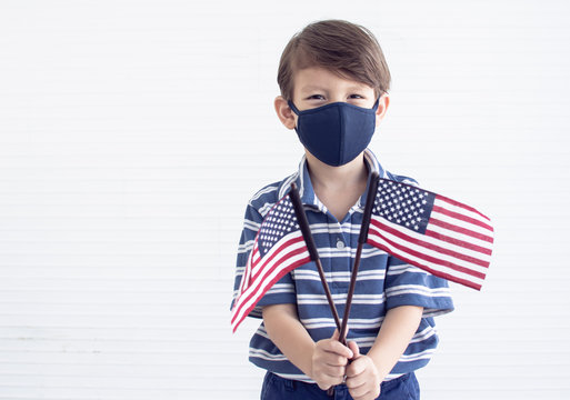 A little boy wearing mask while holding american flags