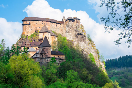 medieval orava castle on the hill. beautiful springtime scenery in dappled light above the river. popular travel destination of slovakia