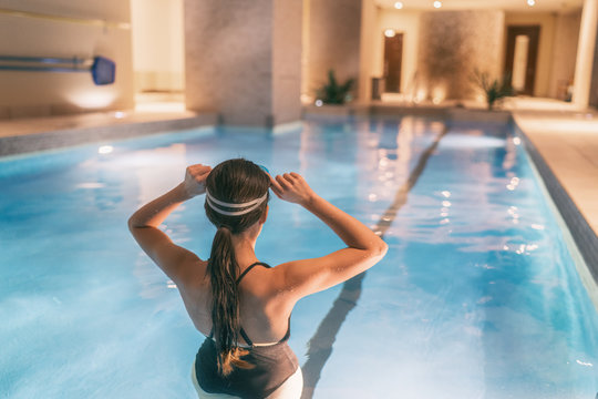 Woman getting ready to swim in indoor swimming pool at hotel or apartment building complex - condo amenities.