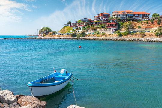 boats in harbor of an old town. popular travel destination. wonderful sunny weather. vintage fishermen houses and old architecture in the distance