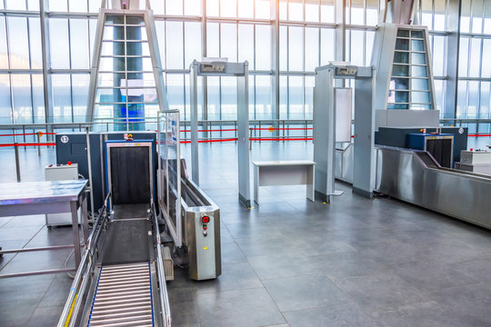 X-ray machine for screening passenger luggage with frame metal detector at the airport check-in counter.
