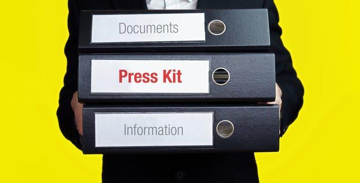 Press Kit – finance/economics. Man carries a stack of 3 file folders. A folder has the label Press Kit. Business, statistics concept
