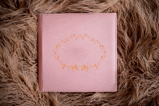 Рink photobook in a leather cover lies on brown fur. Free space for title. Top view