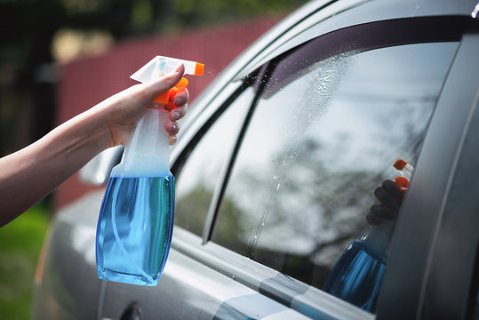 Cleaner is cleaning a car window glass with a rag and detergent close up.