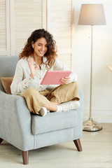 Young woman sitting relaxed in armchair at home and taking part in video conference using tablet PC and earphones