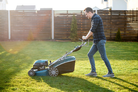 Spring mowing the lawn. Young man in a plaid shirt and jeans mows grass with a lawn mower in the backyard. Side view