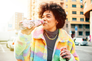 Young beautiful multiethnic woman outdoors drinking from reusable bottle