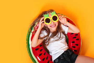 Little girl dressed in a swimsuit and funny pinapple sunglasses lying on an inflatable color ring on yellow background.