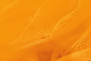 Small mesh fabric on orange background. Shades of orange color