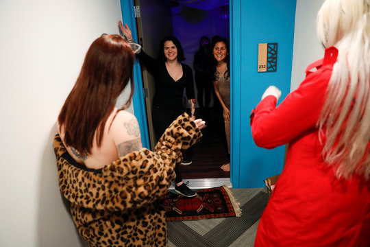 Customers react as exotic dancers deliver food as part of a service offered by the Lucky Devil Lounge strip club in Portland