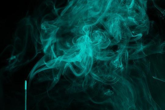 incense smoke. smoldering piece of wood . incense sticks in blue lighting. aromatic smoke . Green colour.