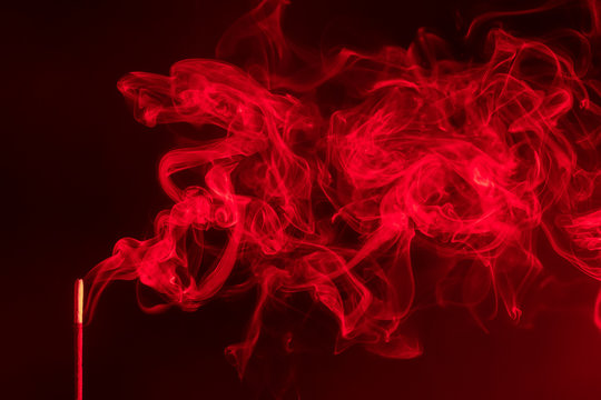 incense smoke. smoldering piece of wood . incense sticks in blue lighting. aromatic smoke . Red colour.