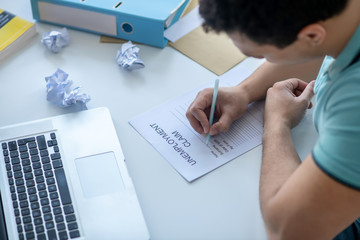 Dark-haired male sitting at his desk, filling in unemployment claim