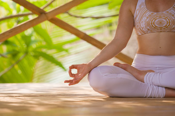 detail of hand of fit and relaxed woman doing yoga and meditation exercise sitting in lotus position outdoors at bamboo hut enjoying nature in beautiful tropical retreat