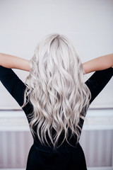 Female back with silver grey ash blonde curly wavy long hair in black dress