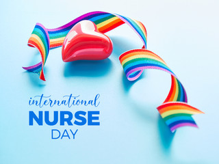 Rainbow ribbon and red ceramic heart on blue mint background. International nurse day thank you card. Symbols of public support for nurses and medical personnel.