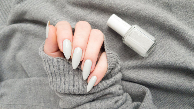 Female hand with long nails and a white gray manicure holds a bottle of nail polish