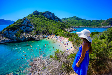 Girl with sun hat at Porto Timoni beach at Afionas is a paradise double beach with crystal clear azure water in Corfu, Ionian island, Greece, Europe Fototapete