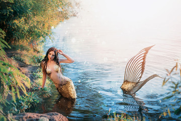 Fantasy woman real mermaid myth goddess of sea. Art goldfish creative costume ocean siren sexy body spa relaxation. mystic spirit of lake river floats swimming in water. sunset nature Magic sun light