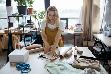 Female tailor working with paper patterns. Small business and self-employed women concept.