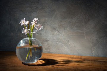 Foto op Canvas Lelie Glass a bowl in the shape of a ball with flowers on the table.