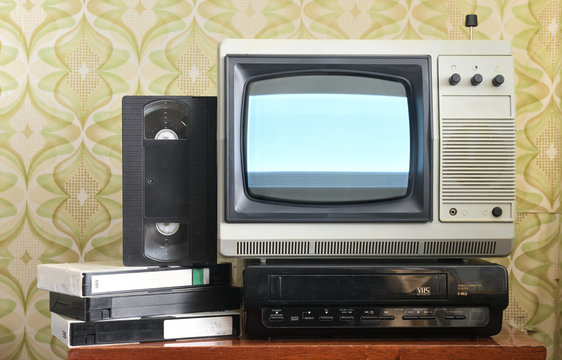 Old silver-colored TV with a VCR on the background of wallpaper.Screen noise.