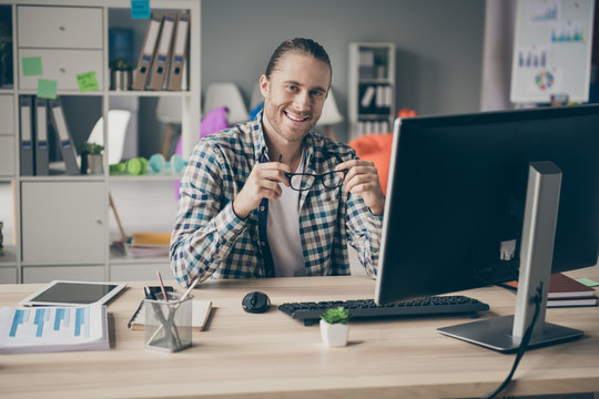 Photo of business handsome guy holding eyeglasses toothy friendly smiling good mood like his new promotion work wear casual outfit sitting chair modern office indoors