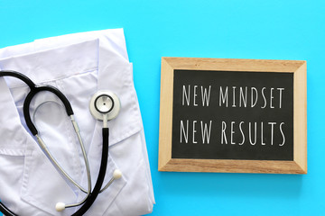 Top view image of table with blackboard and the text new mindset new results. Success and keeping health concept during covid 19 coronavirus outbreak
