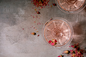 Crystal vintage glasses of pink rose champagne, cider or lemonade with dry rose buds. Grey texture background. Flat lay, space