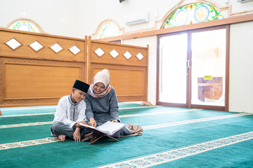 kid learning to read quran with muslim teacher or ustad