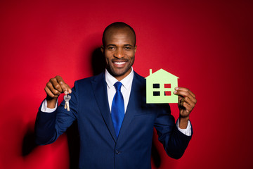 Photo of handsome dark skin business guy hold key chain green paper house real estate agent broker offer sale price wear blue formalwear suit tuxedo isolated red burgundy background