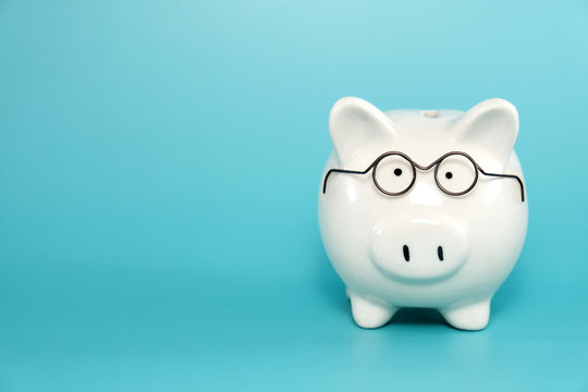 White ceramic piggy bank wearing reading glasses on blue teal background. Concept for money savings plan for retirement, aged society, or financial accounting