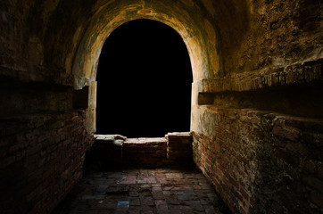 The ancient tunnel, aged construction of historical fortress isolated on black background; Dark in the tunnel, golden glow light or sunset at window. Wall mural
