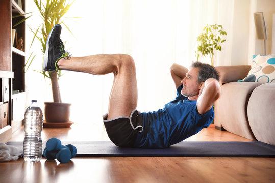 Man doing abdominal exercises lying down in living room
