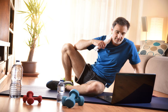 Man wearing sportswear on mat watching videos on a laptop