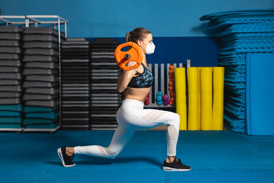 Young fit woman doing lunges at the gym wearing n95 face mask. Fitness worktout with weights under Covid-19 health crisis.