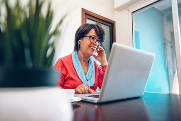 Sixty year old female teacher wearing headphones having online class via video chat on laptop computer. She is sitting on a wooden modern desk at home. Smiling and enjoying communication Fotobehang