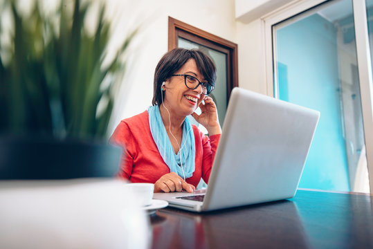 Sixty year old female teacher wearing headphones having online class via video chat on laptop computer. She is sitting on a wooden modern desk at home. Smiling and enjoying communication