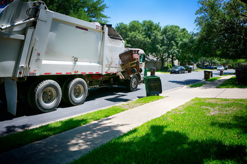Municipal services. Beautiful quiet green neighborhood. Automated modern garbage collector truck loading  waste.