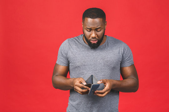 Poverty crisis concept. Upset african american young bearded man in casual holding empty wallet over red background.