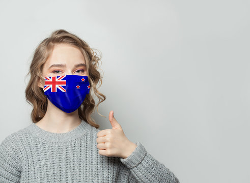 Happy woman in face mask holding thumb up with New Zealand flag background. Flu epidemic and virus protection concept