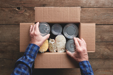 a person packing a donation box with food items Fotomurales