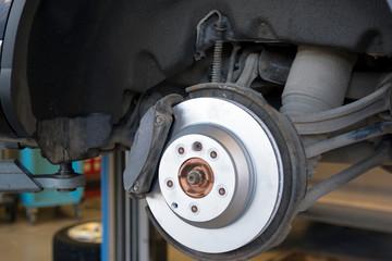 Car repair in a car service. Replacing brakes in a car service. New brake disc close up.