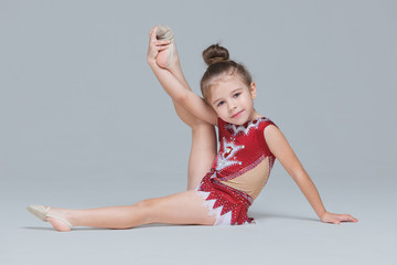 Flexible little girl in beautiful red dress is stretching doing gymnastic exercises on grey background Fototapete