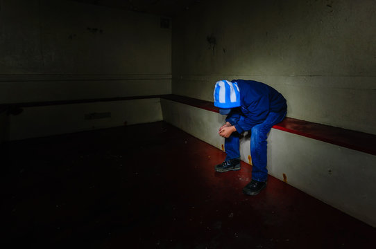 Teenage youth sits remorsefully in a prison cell