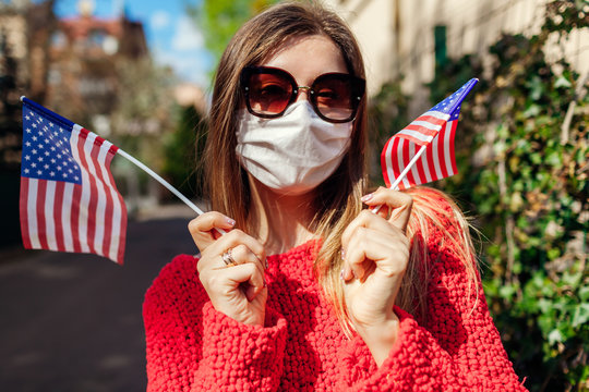Woman wears protective mask outdoors celebrates USA Independence day holds flags during coronavirus covid-19 pandemic.