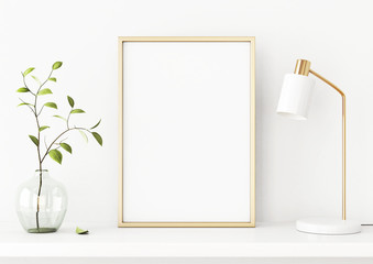 Interior poster mockup with vertical gold metal frame on the shelf with green tree branch in vase and desk lamp on empty white wall background. A4, A3 size format. 3D rendering, illustration.
