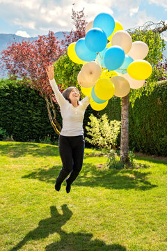 Happy excited senior 65 years old woman holding colorful air ballons jumping and flying in the air in her garden. Pure happiness. Active senior lifestyle concept.