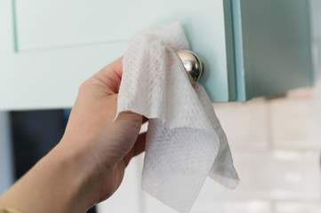 Close-up of hand wiping down knob with disinfectant