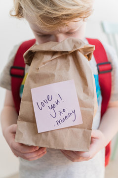 Boy (4-5) peeking into lunch bag with note from mom
